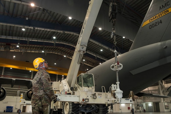 Tech. Sgt. Alejo Blas, 8th Expeditionary Aircraft Maintenance Squadron (EAMS)  lead technical crew chief, helps guide the lifting of a pitch trim actuator with the help of Airmen of the 379th Expeditionary Civil Engineer Squadron (ECES), during a removal, repair and replacement procedure Dec. 18, 2018, at Al Udeid Air Base, Qatar. This is the first time a maintenance procedure like this has been done in U.S. Air Forces Central Command's area of responsibility. Due to safety concerns, Airmen from the 8th EAMS and 379th ECES combined capabilities to ensure the aircraft could be repaired prior to returning to home station. (U.S. Air Force photo by Tech. Sgt. Christopher Hubenthal)