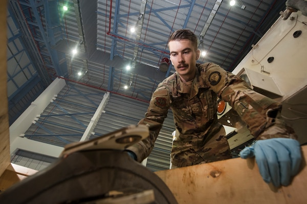Senior Airman Porter Elliott, 8th Expeditionary Aircraft Maintenance Squadron (EAMS) crew chief, prepares a pitch trim actuator for installation in a C-17 Globemaster III Dec. 18, 2018, at Al Udeid Air Base, Qatar. This is the first time a maintenance procedure like this has been done in U.S. Air Forces Central Command's area of responsibility. Due to safety concerns, Airmen from the 8th EAMS and 379th Expeditionary Civil Engineer Squadron combined capabilities to ensure the aircraft could be repaired prior to returning to home station. (U.S. Air Force photo by Tech. Sgt. Christopher Hubenthal)