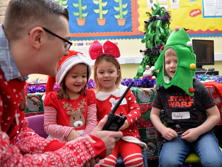 U.S. Air Force Senior Airman Roy Smith, 100th Communications Squadron radio frequency transmissions systems technician, operates a radio as children from Great Heath Academy, Mildenhall, Suffolk, talk with Santa Dec. 18, 2018. A team of three Airmen from RAF Mildenhall visited Great Heath Academy and Beck Row Primary Academy to give early years students a chance to talk to Santa about what presents they would like for Christmas. (U.S. Air Force photo by Karen Abeyasekere)