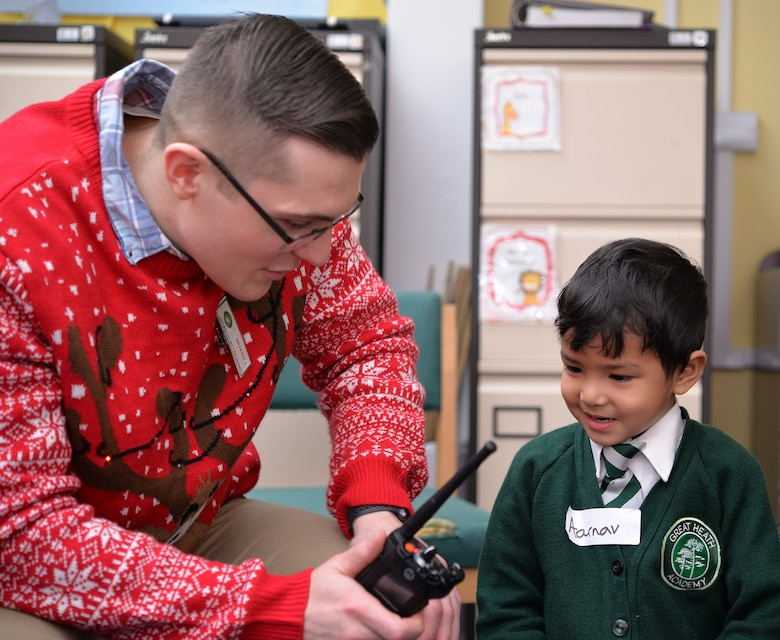 U.S. Air Force Senior Airman Roy Smith, 100th Communications Squadron radio frequency transmissions systems technician, operates a radio as an early years student from Great Heath Academy, Mildenhall, Suffolk, talk with Santa Dec. 18, 2018. A team of three Airmen from RAF Mildenhall visited Great Heath Academy and Beck Row Primary Academy to give students a chance to talk to Santa about what presents they would like for Christmas. (U.S. Air Force photo by Karen Abeyasekere)