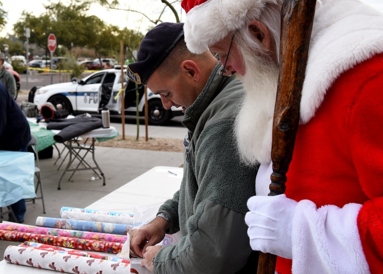 Staff Sgt. Eric Creekmore, 56th Security Force Squadron investigator, wraps presents with Santa at the Glendale Shop with a Cop event, in Glendale, Ariz., Dec. 15, 2018.