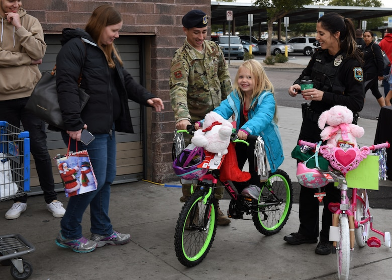 Staff Sgt. Tyler Hendrix, 56th Security Force Squadron military working dog trainer, guides a bike that a child received at the Glendale Shop with a Cop event, in Glendale, Ariz., Dec. 15, 2018.