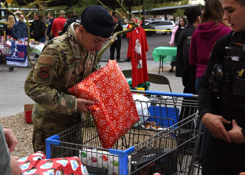 Staff Sgt. Tyler Hendrix, a Security Force Squadron military working dog trainer, places a present inside a cart at the Glendale Shop with a Cop event, in Glendale, Ariz., Dec. 15, 2018.