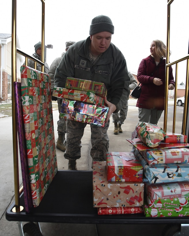 U.S. Air Force Master Sgt. Jarrett Permann, a chaplain assistant in the 119th Wing, loads Christmas gifts onto a cart as he prepares to bring them into the North Dakota Veterans Home, Lisbon, N.D., Dec. 11, 2018.