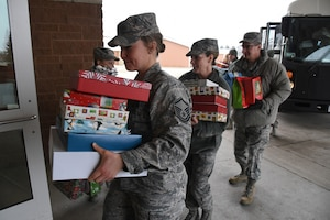 U.S. Air Force members from left to right Master Sgt. Rebecca Johnson, of the 119th Communications Flight, Senior Master Sgt. Roxanne Anderson, of the 119th Wing, and Chief Master Sgt. Duane Kangas, the 119th Wing command chief, carry gifts from a bus into the North Dakota Veterans Home, Lisbon, N.D., Dec. 11, 2018.