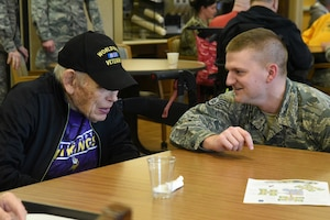 U.S. Air Force Staff Sgt. Nathan Reitan, of the 119th Wing, visits with WWII veteran Robert Olson at the North Dakota Veterans Home, Lisbon, N.D., Dec. 11, 2018.
