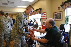 U.S. Air Force Staff Sgt. Nathan Reitan, of the 119th Wing, delivers a Christmas gift to Army Veteran Marvin Hieb at the North Dakota Veterans Home, Lisbon, N.D., Dec. 11, 2018.
