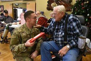 U.S. Air Force Staff Sgt. Blake Lehman, of the 119th Wing, delivers a Christmas present to U.S. Army Veteran Jim Diemert at the North Dakota Veterans Home, Lisbon, N.D., Dec. 11, 2018.