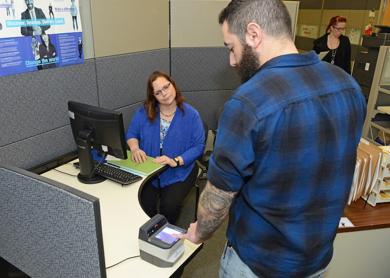 Tammi Hoover, 412th Force Support Squadron Human Resources assistant specialist, watches as a prospective job candidate places his finger on a scanner during a one-day direct hiring event at Bldg. 3000 Dec. 13. (U.S. Air Force photo by Kenji Thuloweit)