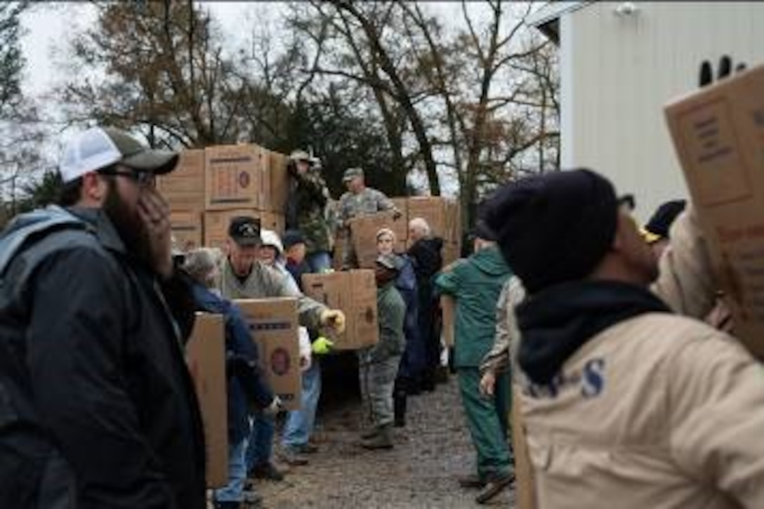 Local community members and Maxwell Airmen work together to unload and sort nearly 700 boxes containing wreaths for the Wreaths Across America ceremony Dec. 14, 2018, at the Alabama National Cemetery, in Montevallo, Alabama. Wreaths Across America is an organization that honors our country's veterans by coordinating wreath laying ceremonies every December. (U.S. Air Force photo by Senior Airman Alexa Culbert)