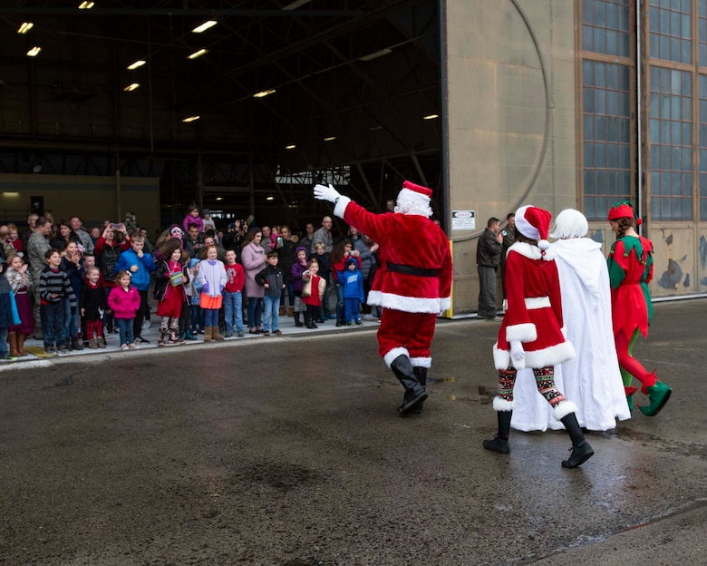 Santa Claus, along with Mrs. Claus and two elves, greet families awaiting them during the 141st Air Refueling Wing's annual Winter Fest Dec. 1, 2018 at Fairchild Air Force Base, Wash. More than 900 Airmen assigned to the 141st are welcome to take part in the festivities along with their families to celebrate the holiday season. (U.S. Air National Guard photo by Staff Sgt. Rose M. Lust/Released)