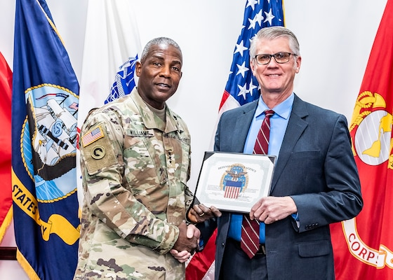 Gen. Williams shakes Ben Roberts hand while both hold certificate.