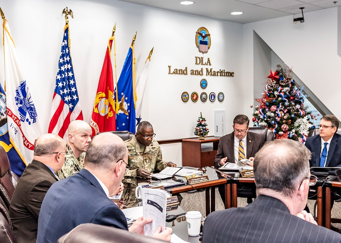Senior leadership from DLA and Land and Maritime sit at a u-shaped table during a meeting