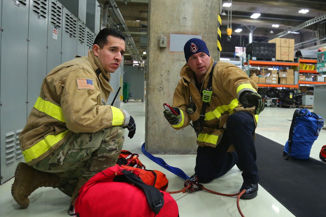Firefighters anchor safety ropes for confined space rescue training at the Western Air Defense Sector Nov. 11, 2018, on Joint Base Lewis-McChord, Washington. Once the simulated patient was secured to a spinal board the firefighters used the ropes as a safety measure when lifting the patient out of the confined space. (U.S. Air National Guard photo by Master Sgt. Tim Chacon)