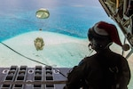 Royal Australian Air Force Sgt. Karl Penny, a C-130J Super Hercules loadmaster with the 37th Squadron out of RAAF Base Richmond, Australia, looks out as the parachute for a Low-Cost, Low-Altitude bundle carries humanitarian aid down to the atoll of Kapingamarangi, Federated States of Micronesia (FSM), during Operation Christmas Drop 2018, Dec. 13, 2018. Every December U.S. Air Force crews from Yokota Air Base, Japan team up with the Japan Air Self-Defense Force (Koku Jietai) and RAAF to airdrop supplies to the Commonwealth of the Northern Marianas, FSM, and the Republic of Palau.