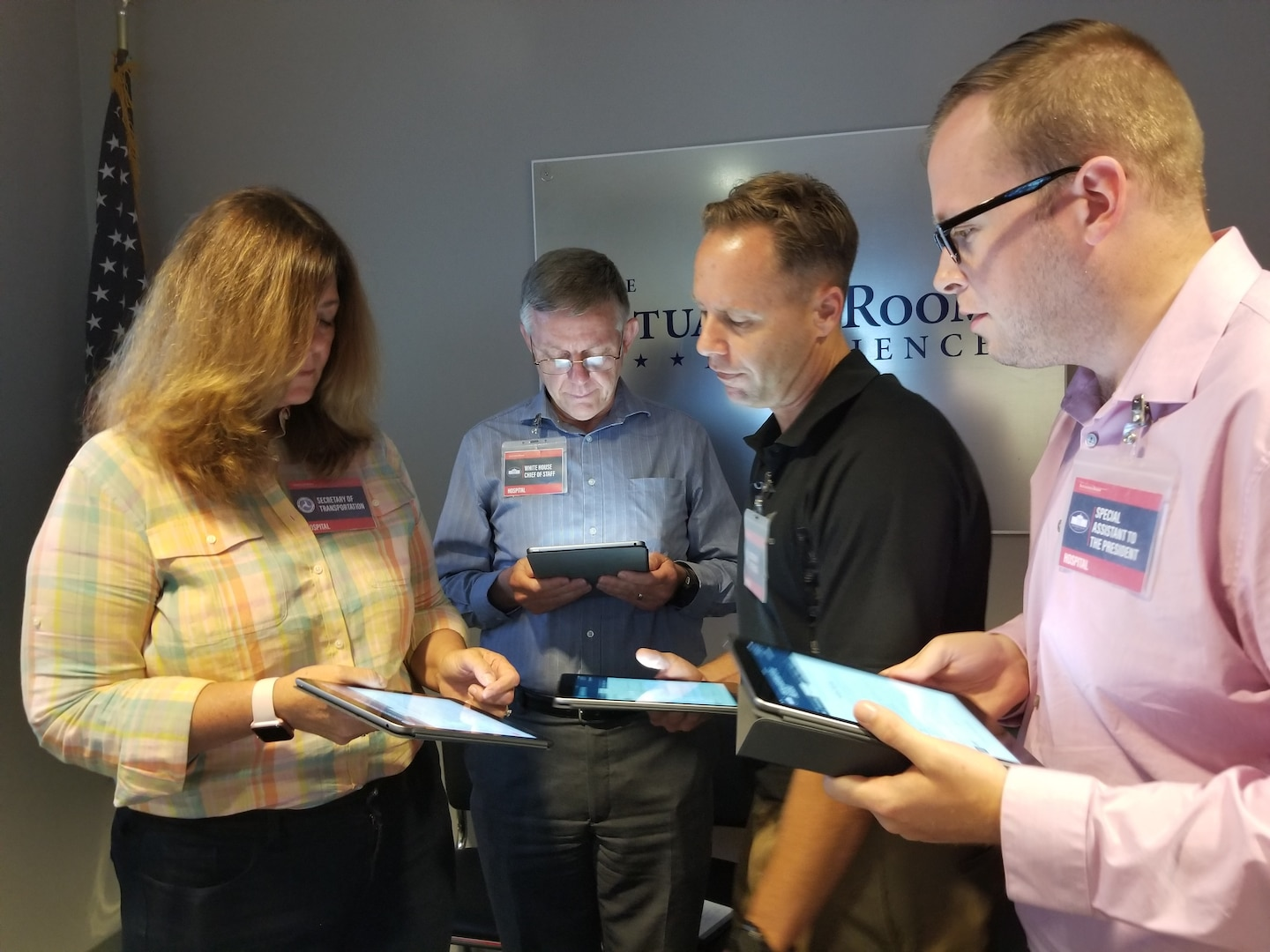 Four people standing in a semi-circle use tablets during a workshop