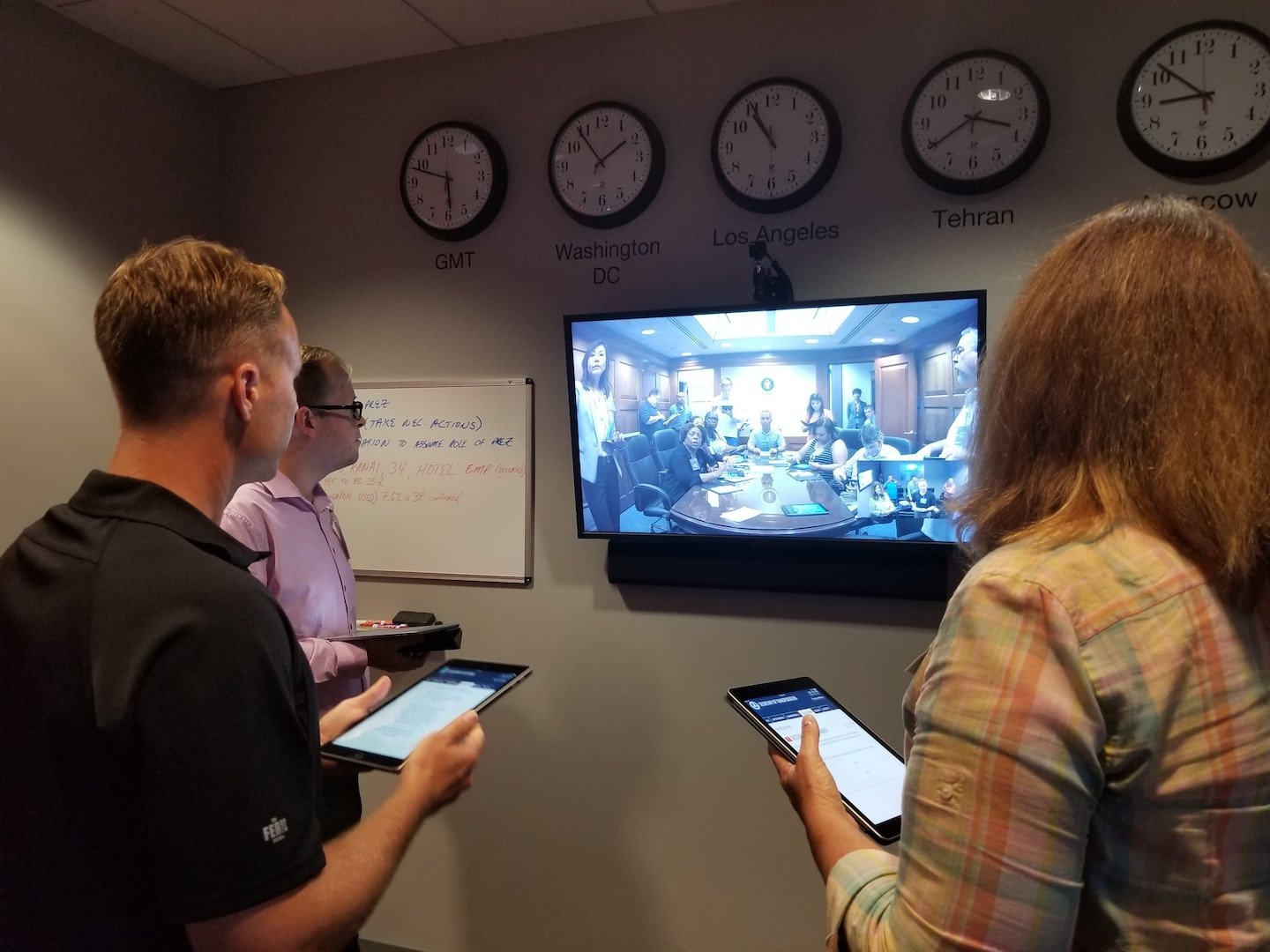 Three people stand in front of a television monitor during a teleconference