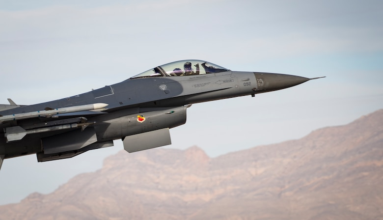 An F-16 Fighting Falcon fighting jet pilot signals after taking off from Nellis Air Force Base, Nevada Dec. 4, 2018. The F-16 is a compact, multi-role fighter aircraft. (U.S. Air Force photo by Airman 1st Class Bryan T. Guthrie)