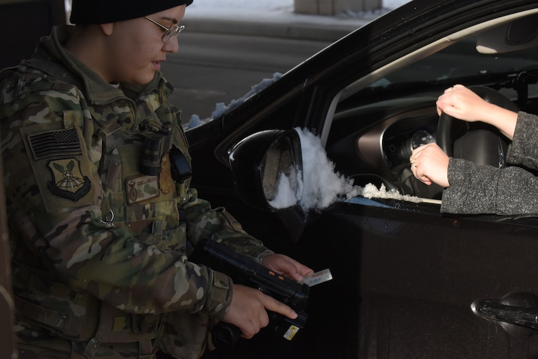 Airman 1st Class Gabriella Sepulveda, a 28th Security Forces Squadron response force member, verifies a common access card at the Liberty Gate on Ellsworth Air Force Base, S.D., Dec. 4, 2018. Each person that comes through the gate gets checked for proper authorization, correct seatbelt wear and that their vehicle has registration on the plates. (U.S. Air Force photo by 2nd Lt. Joshua Sinclair)