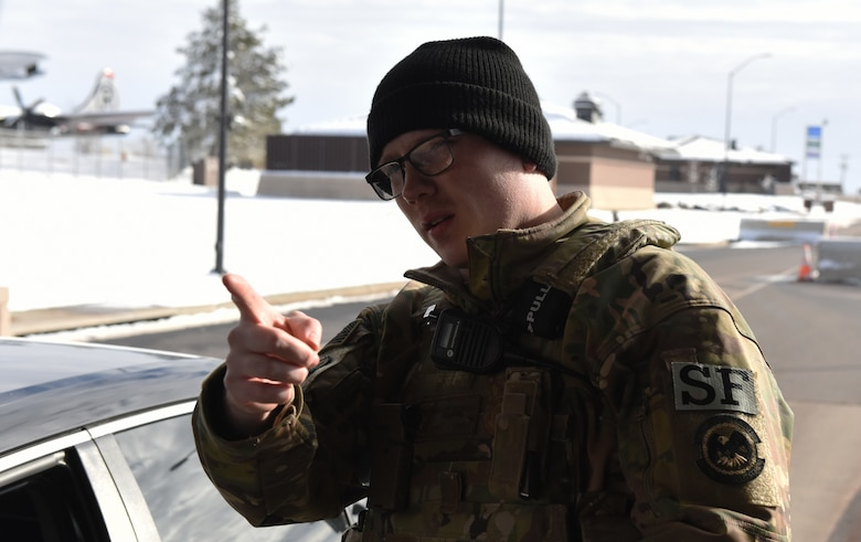 Senior Airman Taylor Tschida, a 28th Security Forces Squadron alarm monitor, gives directions to a person entering Ellsworth Air Force Base, S.D., through Liberty Gate on Dec. 4, 2018. Each person that comes through the gate gets checked for proper authorization, correct seatbelt wear and that their vehicle has registration on the plates. (U.S. Air Force photo by 2nd Lt. Joshua Sinclair)