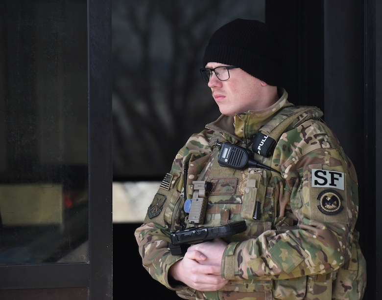 Senior Airman Taylor Tschida, a 28th Security Forces Squadron alarm monitor, stands outside the Liberty Gate waiting for the next car to approach for entry to Ellsworth Air Force Base, S.D., Dec. 4, 2018. Each person that comes through the gate gets checked for proper authorization, correct seatbelt wear and that their vehicle has registration on the plates. (U.S. Air Force photo by 2nd Lt. Joshua Sinclair)