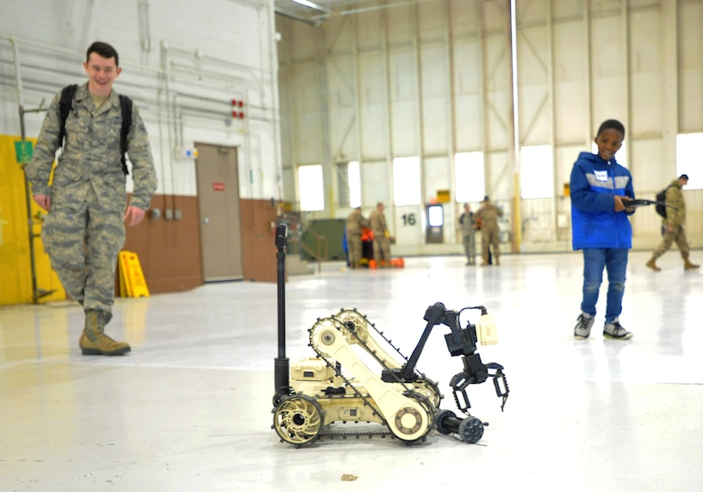 A child from Big Brothers Big Sisters drives a remote controlled vehicle from the Explosive Ordinance Disposal flight Dec. 19, 2018, at McConnell Air Force Base, Kansas. The children spent time in a hangar learning about military working dogs, explosive ordinance disposal, aircrew flight equipment and the KC-135 Stratotanker. (U.S. Air Force photo by Staff Sgt. David Bernal Del Agua)