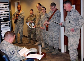 At left, Col. Lance Turner, the 932nd Mission Support Group's multi-talented commander, along with other officers and enlisted leadership, stopped by the 932nd Force Support Squadron customer service waiting area around lunch time in the headquarters building to share some holiday songs Dec 2, 2018, at Scott Air Force Base, Illinois. They sang various melodies during the Unit Training Assembly to help Airmen pass the time in the line. The other highly talented and experienced guitar player at second from right is Master Sgt. Tony Loving, who has been a vocalist and guitarist in a private community band for many years. All the action was captured for historical documentation by Master Sgt. Christopher Parr on his portable tripod and video phone camera system just outside the frame. (U.S. Air Force photo by Lt. Col. Stan Paregien)