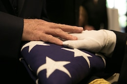 FORT KNOX, Ky. -  A 1st Theater Sustainment Command Soldier presents a folded American flag to a family member of a deceased service member, Nov. 5.