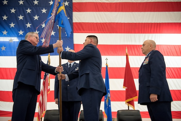 Col. Ashley Groves (center), assumes command of the 123rd Maintenance Group as he accepts the unit's guidon from Col. David Mounkes (left), commander of the 123rd Airlift Wing, during a ceremony at the Kentucky Air National Guard Base in Louisville, Ky., on Dec. 1, 2018. Groves is replacing Col. Ken Dale, who is retiring after more than 38 years of service to the Kentucky Air National Guard. (U.S. Air National Guard photo by Staff Sgt. Joshua Horton)