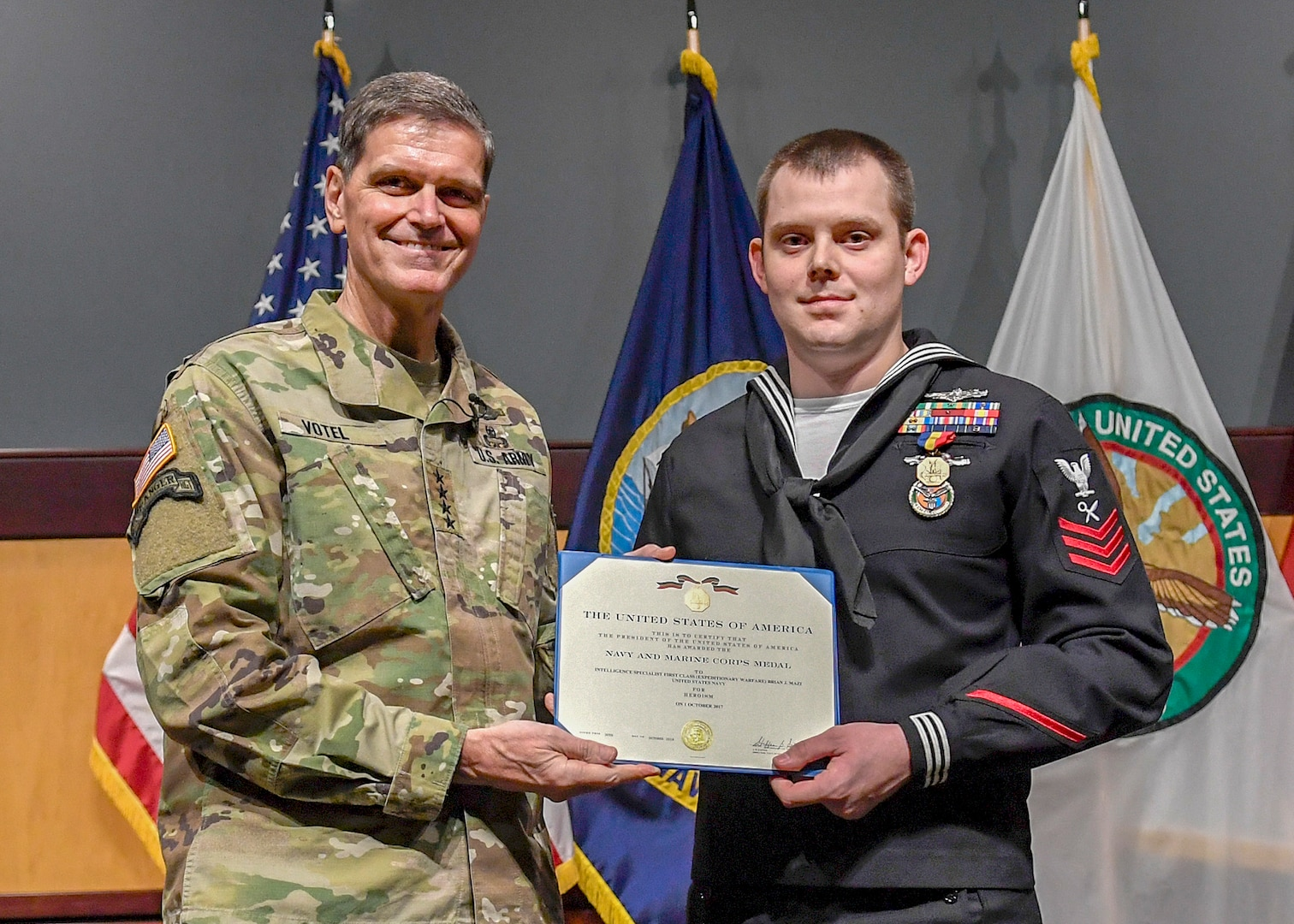 U.S. Army Gen. Joseph Votel, U.S. Central Command commander (left), presents U.S. Navy Petty Officer 1st Class Brian Mazi, USCENTCOM intelligence specialist, with the Navy-Marine Corps Medal on Dec. 18. Mazi was recognized for his heroism during the October 2017 tragedy that left 58 dead and more than 500 wounded at a country music festival in Las Vegas. The award falls between the Distinguished Flying Cross and the Bronze Star in order of merit.