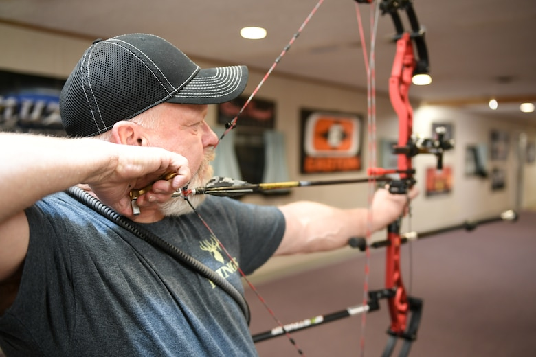 Wayne Willey aims his compound bow at a three-spot target during a Hill Archery Club league night Dec. 13, 2018, at Hill Air Force Base, Utah. Besides access to the clubhouse and ranges 24/7, Hill club members are also invited to participate in several archery events throughout the year. (U.S. Air Force photo by Cynthia Griggs)