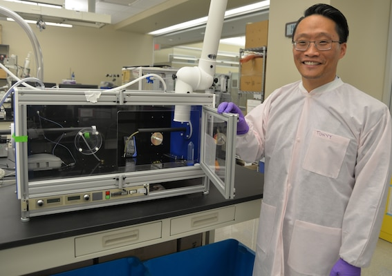 Dr. Tony Yuan, Naval Medical Research Unit San Antonio senior scientist and biomedical engineer at Joint Base San Antonio-Fort Sam Houston, stands next to a second generation electrospinner that was built in 2017 to expand capability of NAMRU-SA to fabricate 3-D nanofibrous scaffolds. The electrospinner uses high voltage electricity as a force to produce and create a nanofibrous scaffold that contains natural fibers, which will be used as a wound dressing, to deliver biomolecules and drugs to heal and treat the wounds of service members injured in combat.