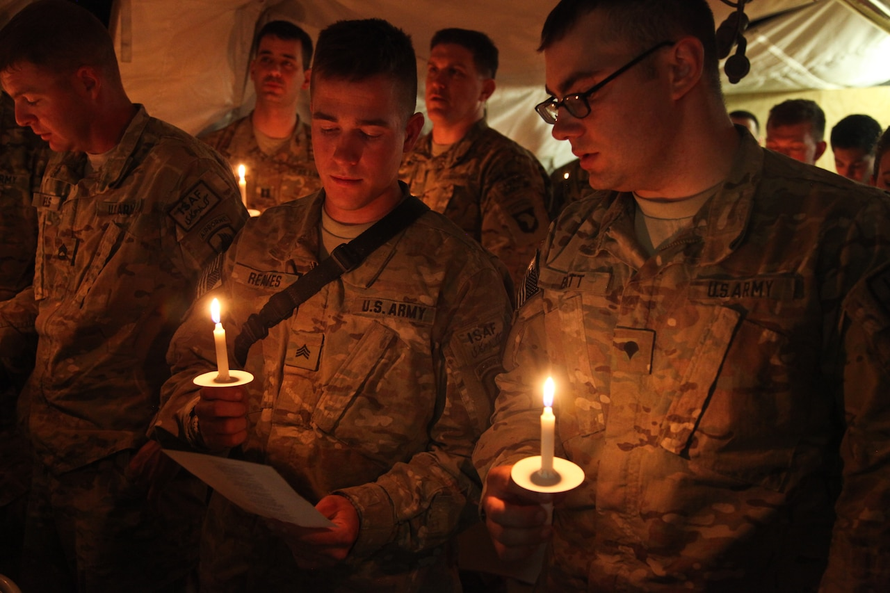 Soldiers hold lit candles.