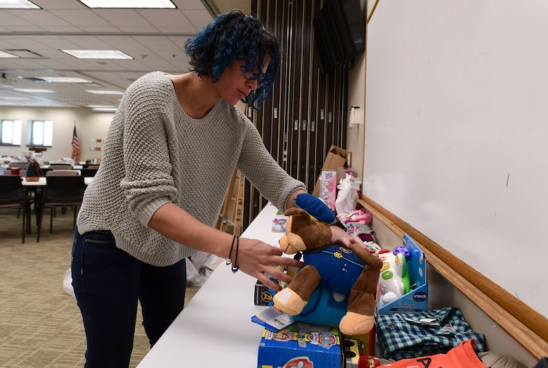 Veronica Quinones, Buckley Spouses Group member, sifts through unassigned donated gifts to find one meeting an Angel Tree recipient's request at Buckley Air Force Base, Colorado, Dec. 19, 2018.