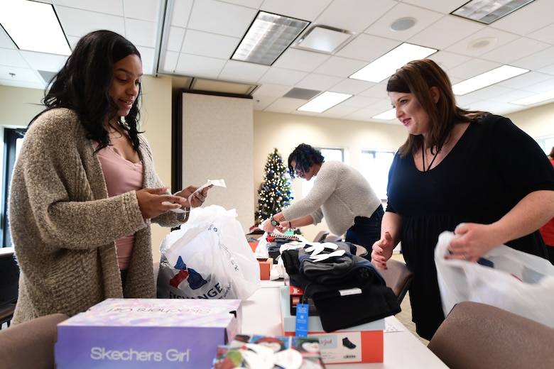 Buckley Spouses Group members ensure donated gifts meet the Angel Tree recipient's requests as best as possible at Buckley Air Force Base, Colorado, Dec. 19, 2018.