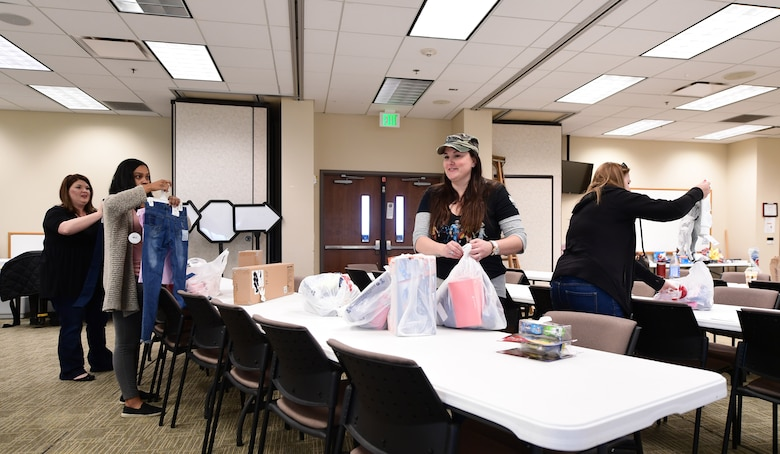 Buckley Spouses Group volunteers sort through various donated gifts provided through the Angel Tree program at Buckley Air Force Base, Colorado, Dec. 19, 2018.