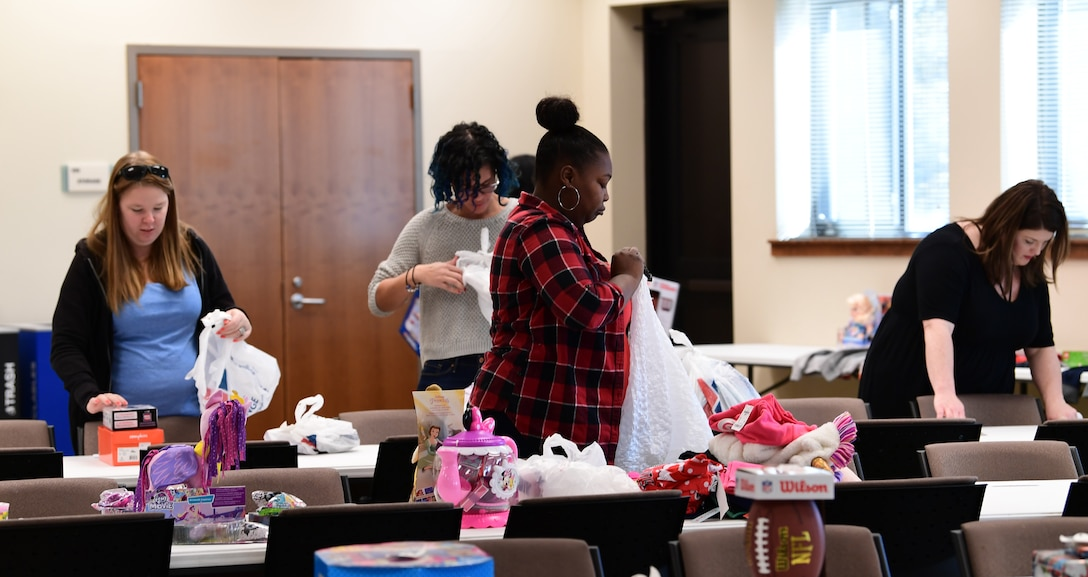 Volunteers sort through gifts donated for over 32 families at Buckley Air Force Base, Colorado, Dec. 19, 2018.