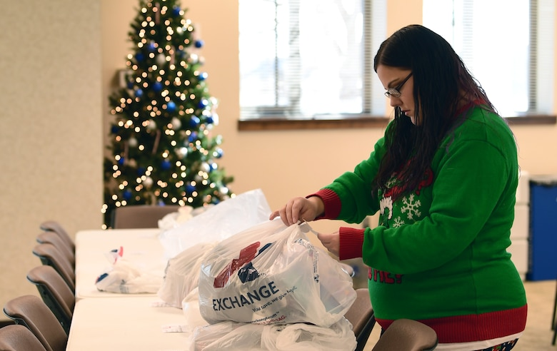 Emily Russell, Buckley Spouses Group member, uncovers a gift donated to the Angel Tree program prior to sorting at Buckley Air Force Base, Colorado, Dec. 19, 2018.