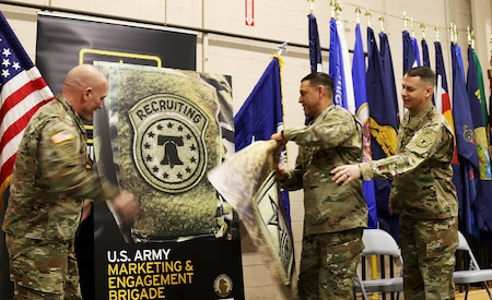 USAREC Commander, Maj. Gen. Frank M. Muth (left), USAMEB Commander, Col. Oscar H. Pintado (center) and USAMEB Command Sergeant Major, CSM Steven R. Laick, peel away a removable graphic of the Army shoulder insignia, revealing the USAREC Bell patch.  USAMEB and MSB Soldiers began wearing the USAREC patch Dec. 18