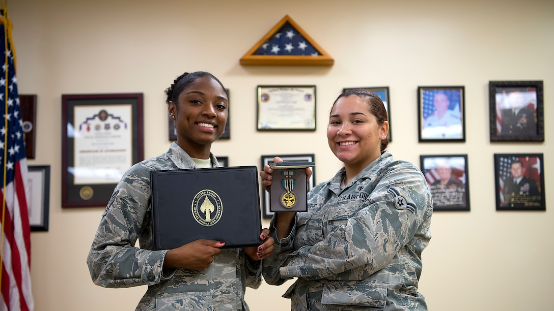 U.S. Air Force Senior Airman Ralecia Ogburn and Airman 1st Class Amari Alexander, 6th Medical Operations Squadron aerospace medical technicians display their Joint Service Commendation honors at MacDill Air Force Base, Fla., Dec. 20, 2018. Ogburn and Alexander distinguished themselves by providing urgent medical treatment and life-saving aid to a critically wounded civilian at a parachute airdrop zone.