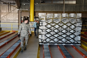 Airman 1st Class Hugh McMackin and Staff Sgt. Ryan Olszewski guide a pallet on the new pallet racking system, Nov. 7, 2018, at Pease Air National Guard Base, N.H. (Photo by Master Sgt. Thomas Johnson, 157th ARW Public Affairs)