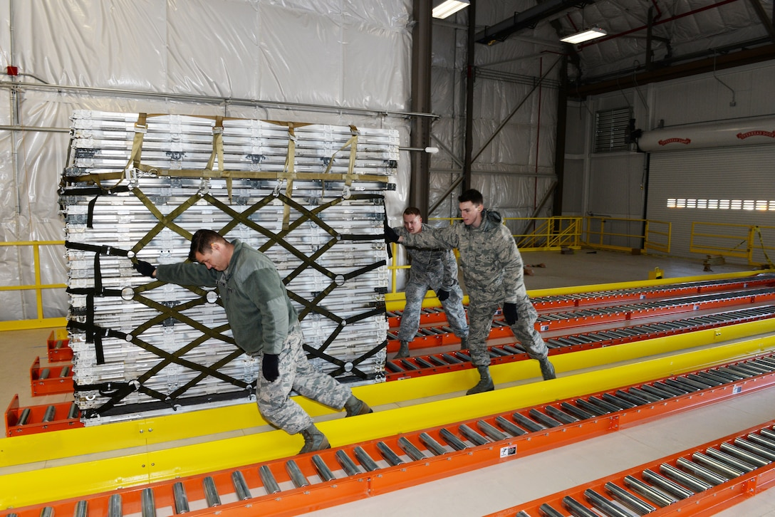 Staff Sgt. Ryan Olszewski, Senior Airman Andrew Poole and Airman 1st Class Hugh McMackin guide a pallet on the new pallet racking system, Nov. 7, 2018, at Pease Air National Guard Base, N.H. (Photo by Master Sgt. Thomas Johnson, 157th ARW Public Affairs)