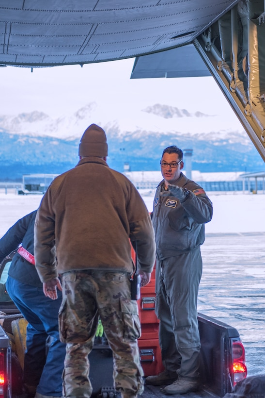 "Senior Airman Dalton Galindo, a loadmaster with the 211th Rescue Squadron, directs cargo movement on a C-130J ""Combat King II"" at Joint Base Elmendorf-Richardson, Alaska, Nov. 30, 2018. In a matter of hours, members of the Alaska Air National Guard's Maintenance and Operation groups turned a planned community engagement into an aerial survey of earthquake damage in Southcentral Alaska, reporting findings to the State of Alaska's Joint Operations Center."