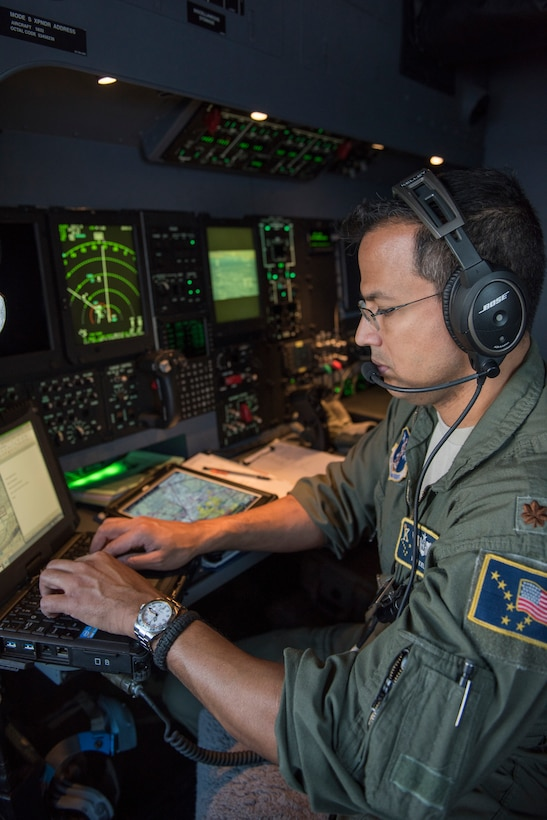 """Maj. Daniel Kelley, a combat systems operator with the 211th Rescue Sqaudron, communicates vital data to the pilots during an aerial damage assessment Nov. 30, 2018, on a C-130J """"Combat King II"""". In a matter of hours, members of the Alaska Air National Guard's Maintenance and Operation groups turned a planned community engagement into an aerial survey of earthquake damage in Southcentral Alaska, reporting findings to the State of Alaska's Joint Operations Center."""