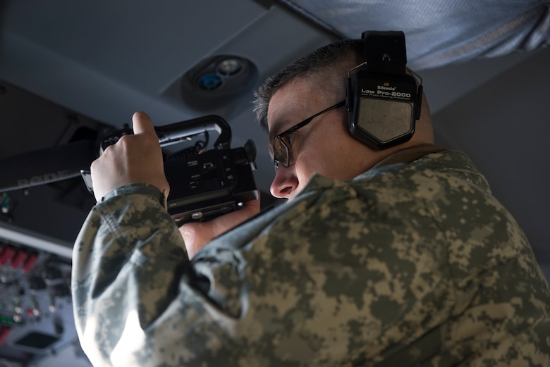 "Army Sgt. David Bedard with the 134th Public Affairs Detachment, Alaska National Guard, records an aerial damage assessment Nov. 30, 2018, on a C-130J ""Combat King II"". In a matter of hours, members of the Alaska Air National Guard's Maintenance and Operation groups turned a planned community engagement into an aerial survey of earthquake damage in Southcentral Alaska, reporting findings to the State of Alaska's Joint Operations Center."