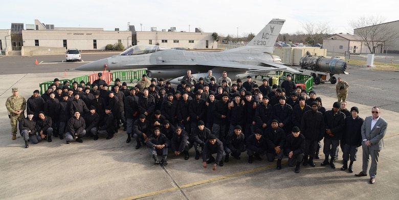 A picture of cadets from the NJ Youth ChalleNGe Academy posing for a group photo in front of a U.S. Air Force F-16C Fighting Falcon.