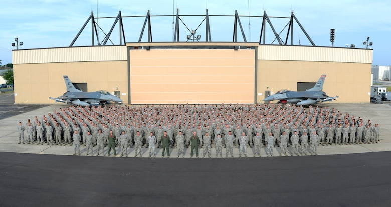 A picture of members of the 177th Fighter Wing of the New Jersey Air National Guard posing for a group photo at the Atlantic City Air National Guard base in front of two U.S. Air Force F-16C Fighting Falcons and a hangar.