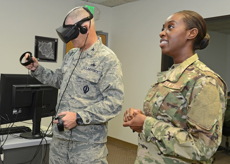 Staff Sgt. Nori Sannoh, 432nd Maintenance Group, Creech Air Force Base, Nevada, guides Col. Lawrence Havird, 412th Maintenance Group commander, in a demonstration that showed how maintainers can train using virtual reality. (U.S. Air Force photo by Kenji Thuloweit)