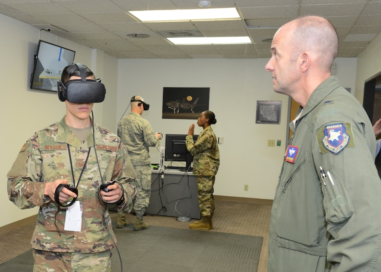 Tech. Sgt. Jeremy Neilson, 412th Aircraft Maintenance Squadron (left), prepares a virtual reality program for Brig. Gen. E. John Teichert III, 412th Test Wing commander, at the new F-35 virtual reality room Dec. 20. Neilson showed wing leadership how virtual reality can be used in conducting maintenance training for F-35 fighters. (U.S. Air Force photo by Kenji Thuloweit)