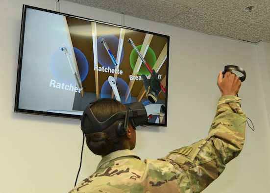 Staff Sgt. Nori Sannoh, 432nd Maintenance Group, Creech Air Force Base, Nevada, demonstrates a virtual reality program for 412th Test Wing leadership Dec. 20. Sannoh assisted with the demonstration that showed how maintainers can train using virtual reality. (U.S. Air Force photo by Kenji Thuloweit)